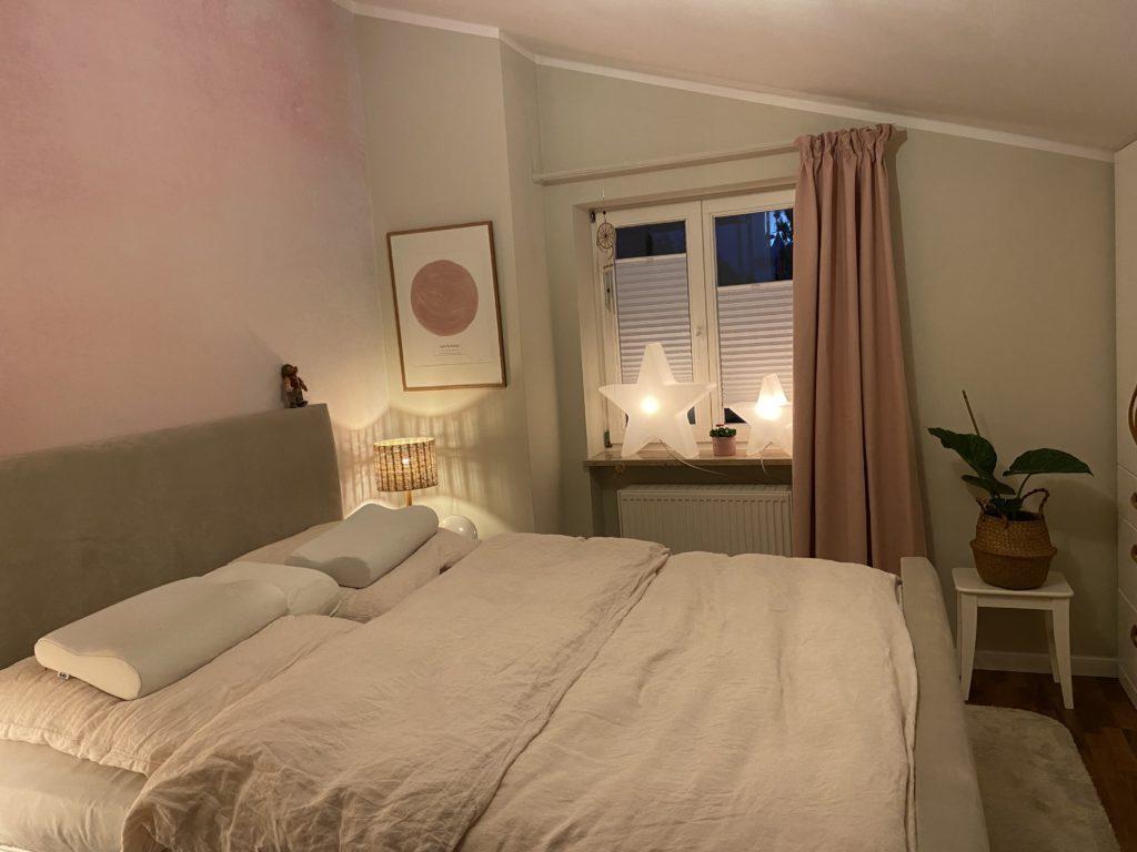 Feng-Shui-Optimierung im Schlafzimmer. Polsterbett an der Innenwand mit Kopf- und Fußteil. Tapete in Rosé-Ton hinter dem Bett. Vorhang in Rosé-Ton und eine Pflanze mit runden Blättern.